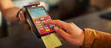 Purchase being made with a credit card on a card reader.